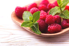 Fresh organic ripe raspberry with mint leaves in tray. On wooden table background. Concept of healthy food. Top view Stock Photography