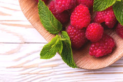 Fresh organic ripe raspberry with mint leaves in tray Stock Photo