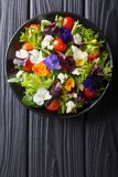 Fresh organic salad from edible flowers with lettuce, tomatoes a. Nd cream cheese close-up on the table. Vertical top view from above royalty free stock image