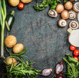 Fresh organic seasonal garden vegetables for cooking on rustic wooden background, top view, frame, place for text.  Vegan food Royalty Free Stock Image