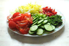 Fresh organic sliced vegetables on the white plate on the wooden table. Close up, selective focus. Stock Photography