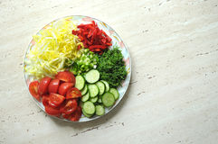 Fresh organic sliced vegetables on the white plate on the wooden table. Top view, flat lay. Royalty Free Stock Photo