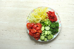 Fresh organic sliced vegetables on the white plate on the wooden table. Top view, flat lay. Royalty Free Stock Photos