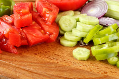 Fresh organic sliced vegetables on a wooden board. Sliced tomatoes, cucumber, green pepper and red onion on a wooden cutting board. Preparing fresh and healthy Stock Photos