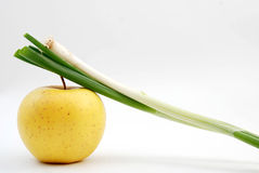 Fresh organic spring onion on yellow apple Stock Image