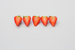 Fresh organic strawberries halved and arranged in a line on a white background. Fresh organic strawberries with green leaves arranged in a line on a white stock image