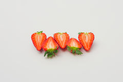 Fresh organic strawberries halved and arranged on a white background. Fresh organic strawberries with green leaves, halved and decorated on a white background stock photos