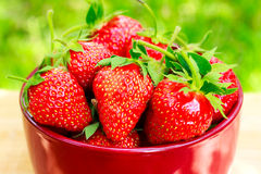 Fresh, organic strawberry in bowl, on wooden table, outdoors. Selective focus Stock Photos