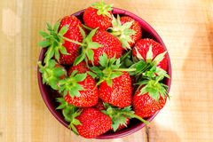 Fresh, organic strawberry in bowl, on wooden table, top view. Flat image Royalty Free Stock Images