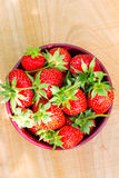 Fresh, organic strawberry in bowl, on wooden table, top view. Flat image Royalty Free Stock Photo