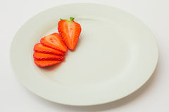 Fresh organic strawberry sliced and arranged in a white plate. Fresh, organic strawberry with green leaves, on a white plate. Fresh spring and summer fruit on a royalty free stock images