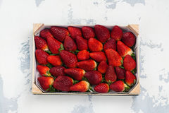 Fresh organic strawberry. In a wooden box on white stone background. Space for text. Top view Stock Photos