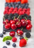 Fresh organic summer berries mix on black marble board on light kitchen table background. Raspberries, strawberries, blueberries,. Blackberries and cherries royalty free stock images