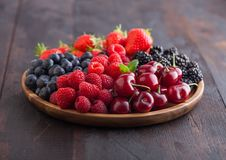 Fresh organic summer berries mix in round wooden tray on dark wooden table background. Raspberries, strawberries, blueberries,. Blackberries and cherries. Top stock photos