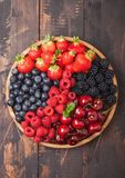 Fresh organic summer berries mix in round wooden tray on dark wooden table background. Raspberries, strawberries, blueberries,. Fresh organic summer berries mix stock image