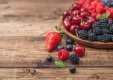 Fresh organic summer berries mix in round wooden tray on light wooden table background. Raspberries, strawberries, blueberries,. Blackberries and cherries. Top royalty free stock photo