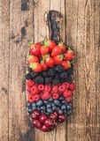 Fresh organic summer berries mix on vintage wooden chopping board on light wooden table background. Raspberries, strawberries,. Blueberries, blackberries and stock images