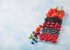 Fresh organic summer berries mix on white marble board on blue kitchen table background. Raspberries, strawberries, blueberries,. Blackberries and cherries. Top stock image