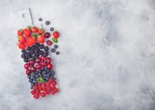 Fresh organic summer berries mix on white marble board on light kitchen table background. Raspberries, strawberries, blueberries,. Blackberries and cherries stock photography