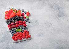 Fresh organic summer berries mix on white marble board on light kitchen table background. Raspberries, strawberries, blueberries,. Blackberries and cherries stock photo