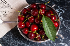 Fresh organic sweet cherry and big green leaf in steel colander Stock Images