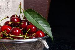 Fresh organic sweet cherry in steel colander on dark marble back Royalty Free Stock Photo