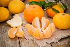 Fresh organic tangerines and peeled slices Stock Photos