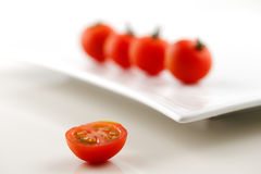 Fresh organic tomatoes and a half of tomato in the foreground Royalty Free Stock Images