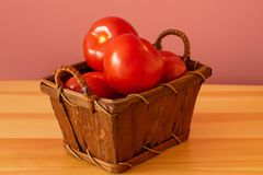 Fresh organic tomatoes ready to eat. Organic tomatoes in a small brown basket with a pink background Royalty Free Stock Images