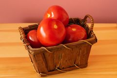 Fresh organic tomatoes ready to eat. Organic tomatoes in a small brown basket with a pink background Royalty Free Stock Photos