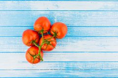 Fresh Organic Tomatoes With Waterdrops On Blue And White Painted. Background With Empty Space High Contrast Top View stock images
