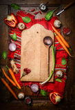 Fresh organic vegetables around old cutting board with wooden spoon on rustic napkin and wooden background. Top view, frame. Stock Photo