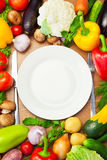 Organic Vegetables Around White Plate with Knife and Fork Royalty Free Stock Photos