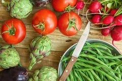 Fresh Organic Vegetables Artichokes Green Beans Tomatoes Red Radish Broccoli Eggplants on Weathered Wood Garden Kitchen Table. Vegan Clean Eating Mediterranean Royalty Free Stock Photography