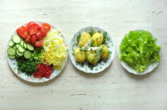 Fresh organic vegetables and boiled new potatoes on three plates Stock Images