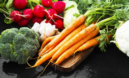 Fresh organic vegetables bowl with carrots, cauliflower, broccol. I, tomatoes, mushrooms, radishes on wooden board Royalty Free Stock Photos