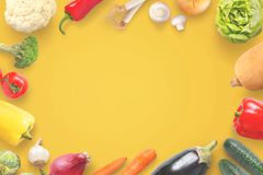 Fresh organic vegetables composition on yellow table with copy space in the middle Stock Photos