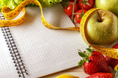 Fresh organic vegetables and fruits, open blank notebook and pen Stock Images