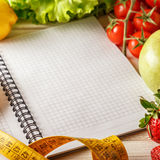 Fresh organic vegetables and fruits, open blank notebook and pen Stock Photography