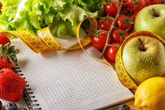 Fresh organic vegetables and fruits, open blank notebook and pen Royalty Free Stock Photo