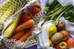 Fresh organic vegetables and fruits in reusable shopping bags royalty free stock image
