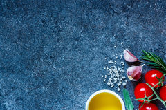 Fresh organic vegetables. Ingredients (olive oil, sea salt, tomatoes, garlic cloves, rosemary) on dark slate background. Fresh organic vegetables. Cooking Royalty Free Stock Photography
