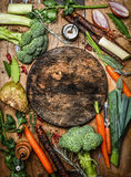 Fresh organic vegetables ingredients for soup or broth around round rustic blank cutting board, top view. Stock Photos