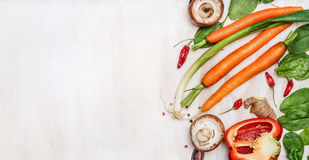 Fresh organic vegetables ingredients for tasty cooking on white wooden background, top view, place for text. Stock Image
