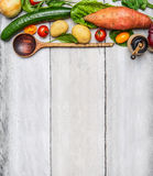 Fresh organic vegetables ingredients and wooden spoon on rustic wooden background, top view. Royalty Free Stock Images