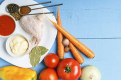 Fresh organic vegetables from rustic garden for dietary garnish and raw chicken wings on white plate. Top view on wooden table wit. H copy space royalty free stock photo