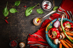 Fresh organic vegetables and seasoning ingredients in basket on rustic kitchen table with spoon and oil. Royalty Free Stock Image