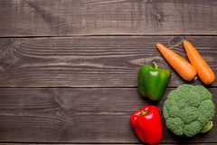 Fresh organic vegetables on wooden background, copy space. Carrot, pepper, broccoli top view stock photography