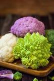 Fresh organic white and purple cauliflower, broccoli, romanesco. In wooden bowl Royalty Free Stock Photo