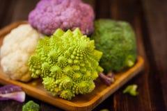 Fresh organic white and purple cauliflower, broccoli, romanesco. In wooden bowl Royalty Free Stock Photography